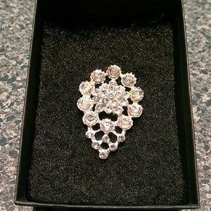 Silver rhinestone brooch.